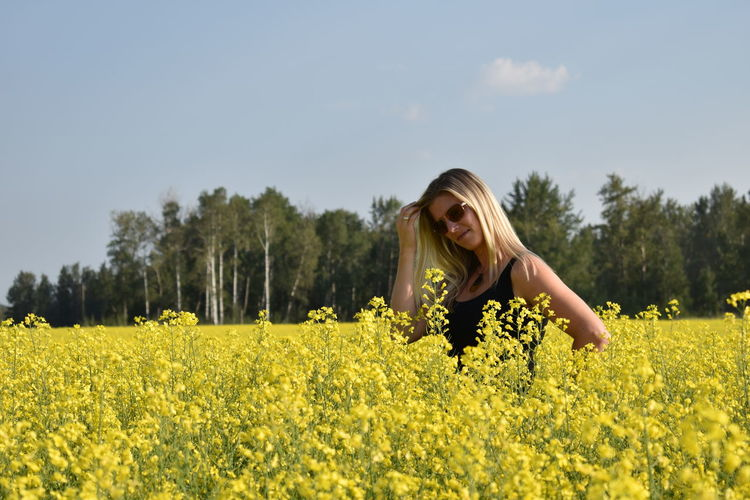 Woman standing amidst yellow flowering plants