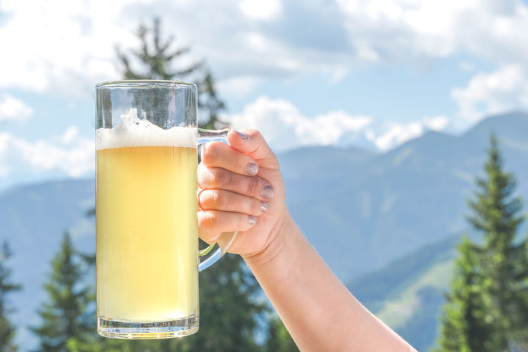 Close-up of hand holding beer glass against mountain