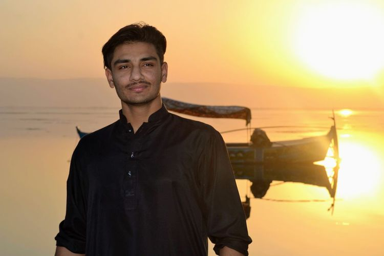Portrait of young man standing against sea during sunset