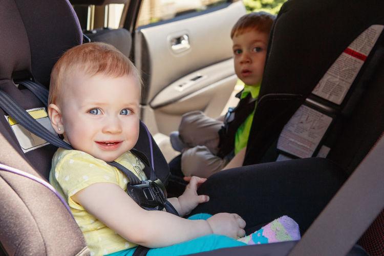 Portrait of cute siblings sitting in car