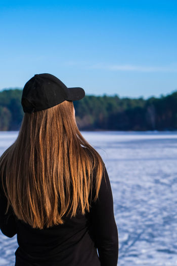 Young female woman back to the camera with long hair in a snow landscape. happy hipster