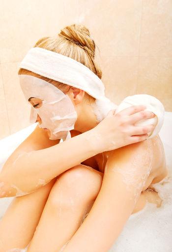 Woman Rubbing Shoulder With Sponge In Bathtub At Bathroom