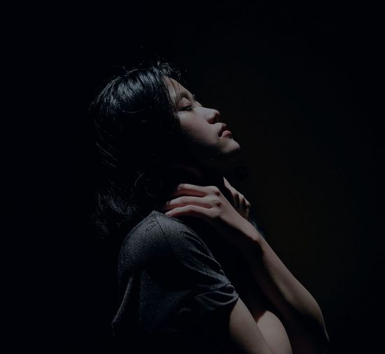 Portrait of woman looking away against black background