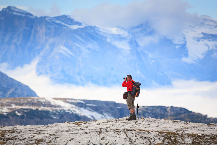 Side view of man photographing while standing against snowcapped mountains