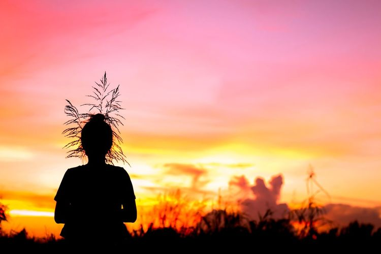 Rear view of silhouette woman standing on field against sky during sunset