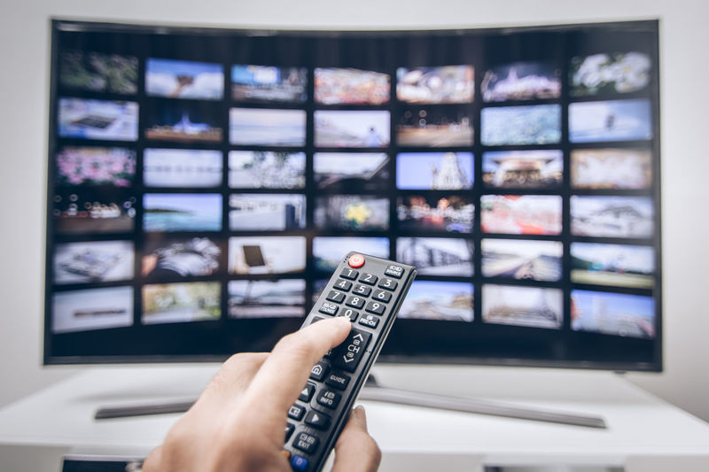 Cropped Hand Of Man Holding Remote Control At Home