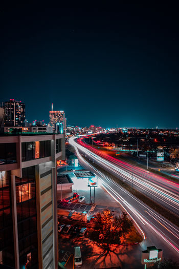 Light trails on street amidst buildings against sky at night