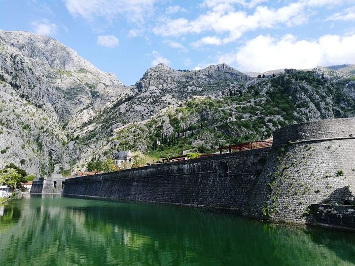Low angle view of bay of kotor mountains against sky