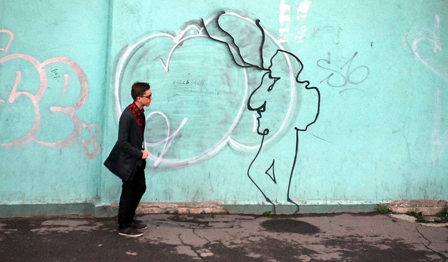 Side view of man standing against graffiti wall