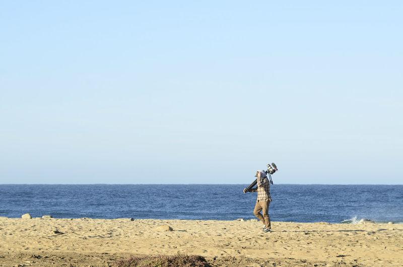 Cameraman walking on ocean beach early morning carrying his video camera baja california sur, mexico
