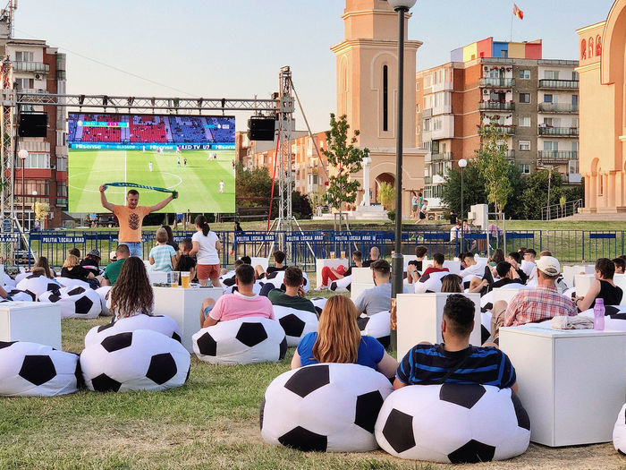 Group of people sitting on soccer field in city
