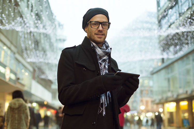 Portrait of man using digital tablet while standing in city