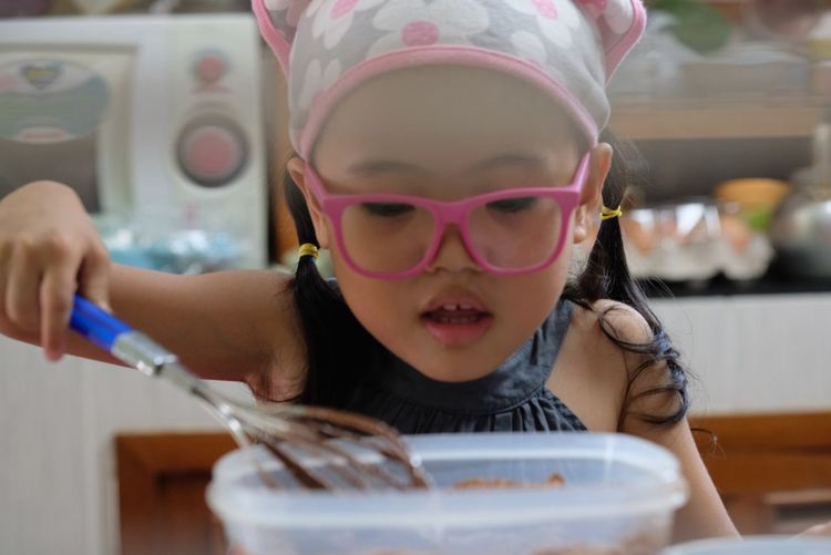 Close-up of cute girl preparing food on table