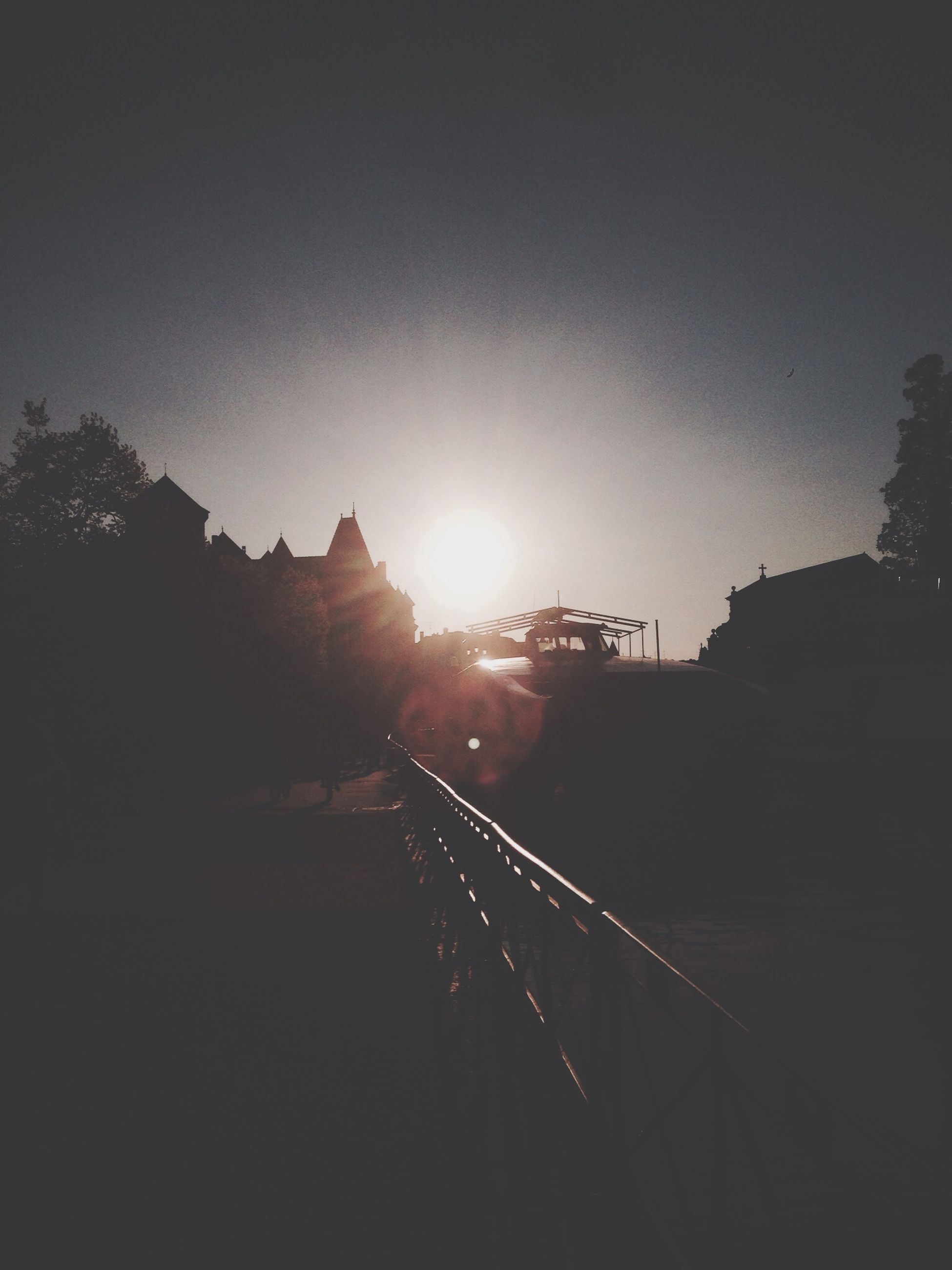 sun, clear sky, sunset, built structure, lens flare, silhouette, sunlight, copy space, architecture, sky, transportation, sunbeam, building exterior, tree, railroad track, outdoors, no people, nature, the way forward, dark