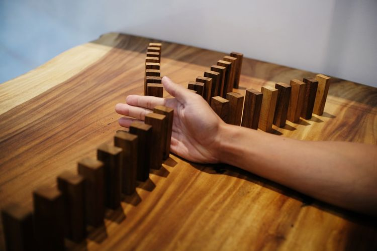 Close-Up Of Cropped Hand Playing Domino On Table