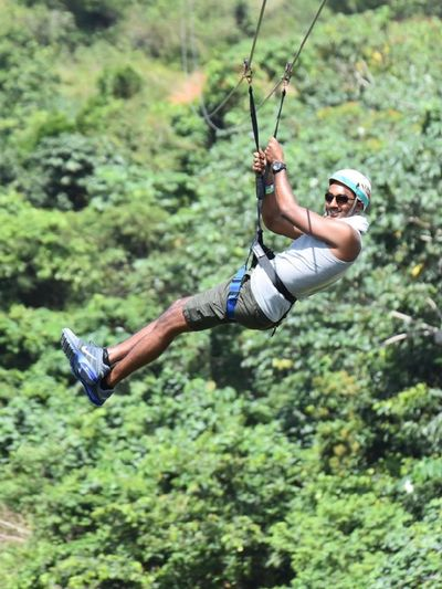 Full Length Of Man Hanging On Zip Line In Forest