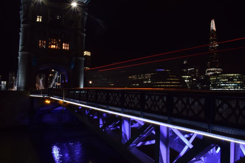 Illuminated suspension bridge in city at night