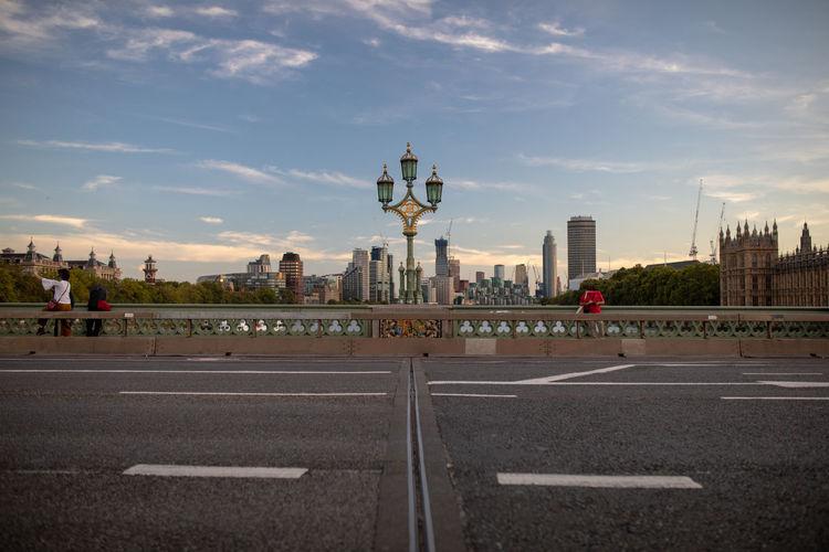 People on bridge in city against blue sky