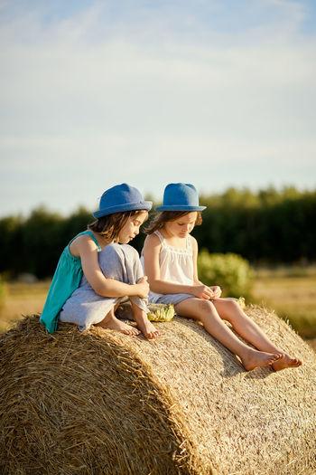 Friends wearing hats sitting on hay bale against sky