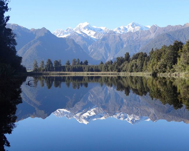 Mirror image lake blue idyllic Reflection Water Lake Mountain Nature Sunset Snow Outdoors Scenics Landscape Mountain Range Sky Beauty Beauty In Nature No People Cold Temperature Tree Natural Parkland Day