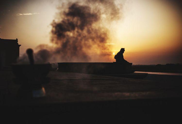 Silhouette person sitting against orange sky