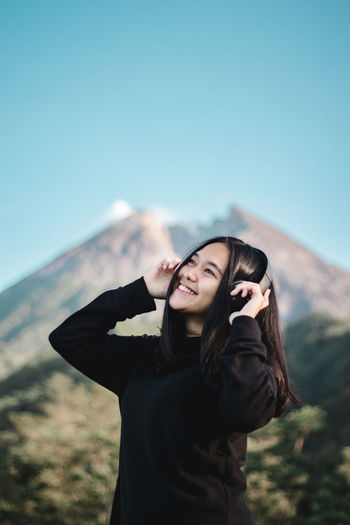 Smiling woman listening music against clear sky