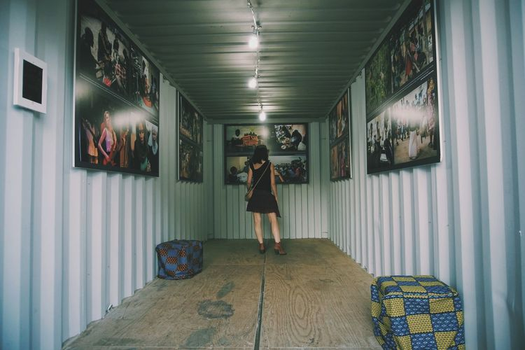 Rear view of woman standing by photographs
