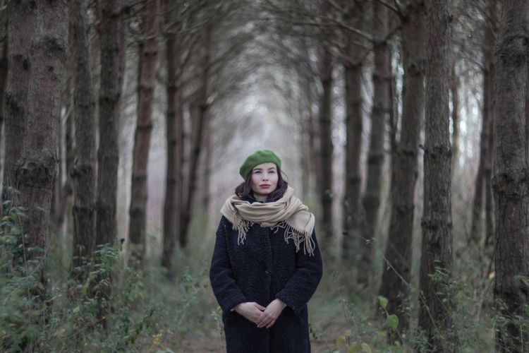 Young woman standing by tree trunk in forest during winter