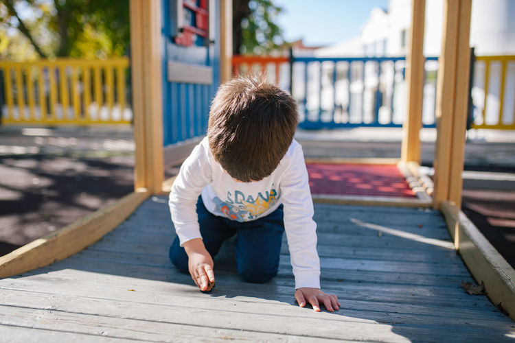 Boy playing on wooden floor at playground