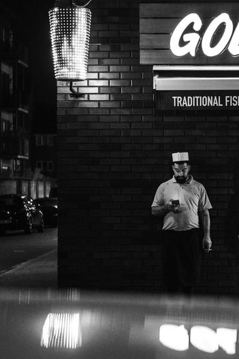 Man standing by text on wall in city at night