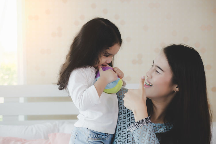 Mother gesturing with daughter holding ball at home
