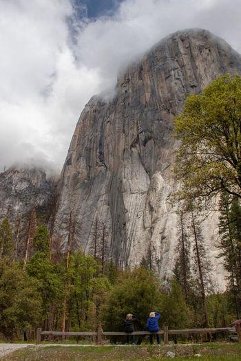 Rear view of people walking on rocky mountain
