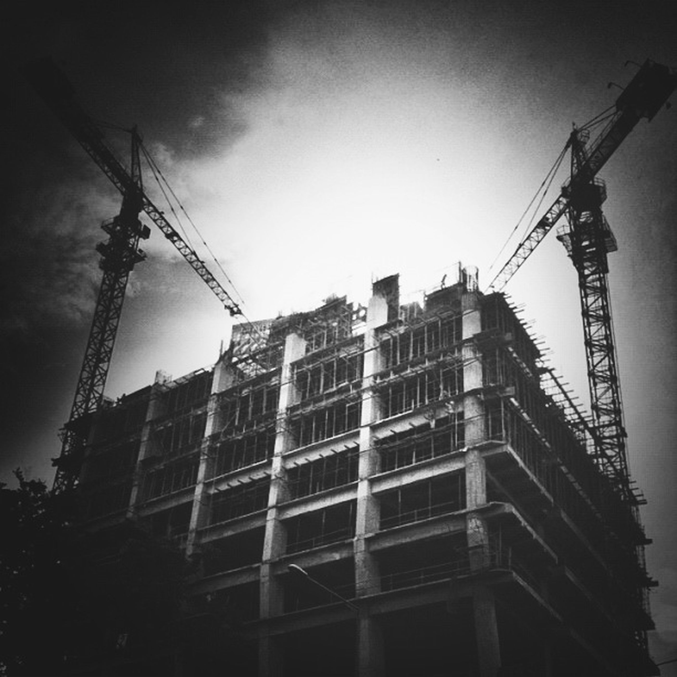 architecture, built structure, low angle view, building exterior, sky, construction site, crane - construction machinery, development, city, building, tall - high, construction, tower, outdoors, clear sky, no people, day, incomplete, power line, residential building