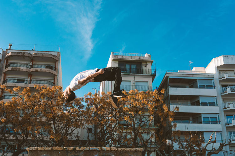 Building Exterior Built Structure Architecture One Person Sky Building Day Tree Nature Plant Outdoors Real People City Low Angle View Men Lifestyles Sunlight Leisure Activity Full Length Apartment