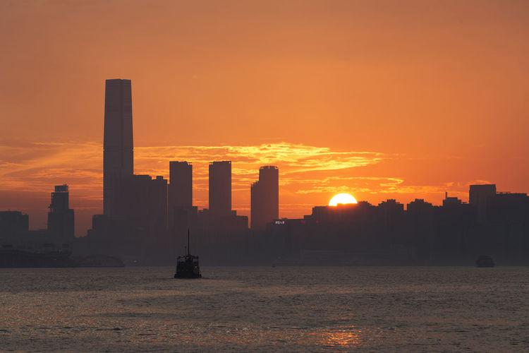 Silhouette buildings against orange sky during sunset