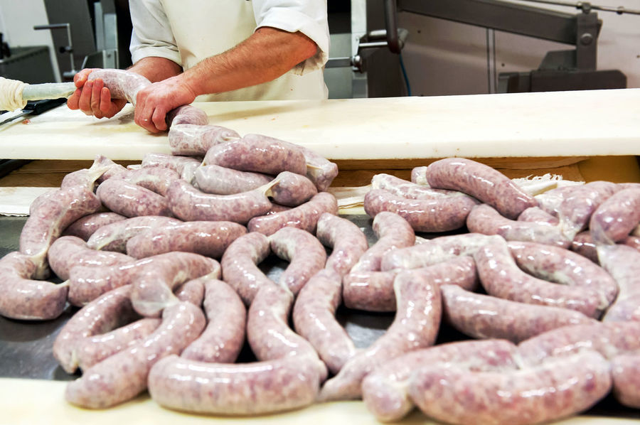 utcher making fresh spicy salami sausage dividing the long freshly filled casing into portions for drying and curing, close up view on the newly filled membrane Beef Butcher Pork Butcher Casing Meat Occupation Preparation  Preparing Food Product Salami Sausage