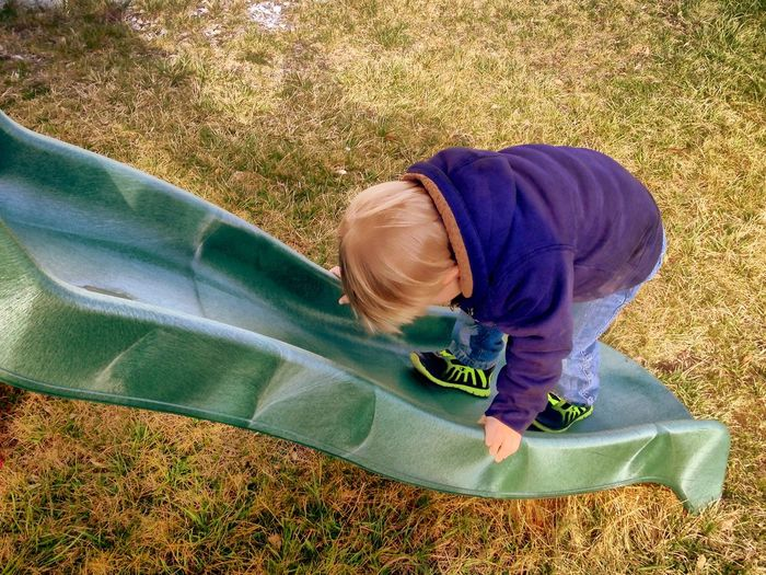Rear view of boy on slide at park