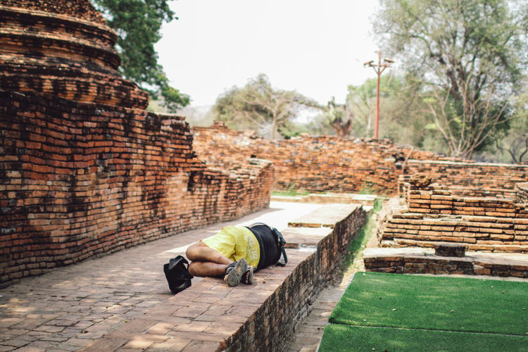 Tourism sleeping in temple ruins of Wat Mahathat in Ayutthaya Historical Park, Archaeological site in Thailand One Person Architecture Wall Full Length Day Built Structure Real People Nature Lifestyles Building Exterior History Plant Relaxation Sky Staircase The Past Men Leisure Activity Brick Outdoors Stone Wall Architecture Culture Temple Travel Ancient Buddhism Old Statue ASIA Thailand Building Tourism Buddha Meditation Sculpture Buddhist Religion Asian  Worship Landmark Spirituality Sleeping Religious  Famous Place Meditating Historical Heritage Monument Unesco