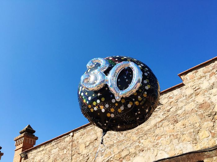Low angle view of balloon by old building against clear blue sky