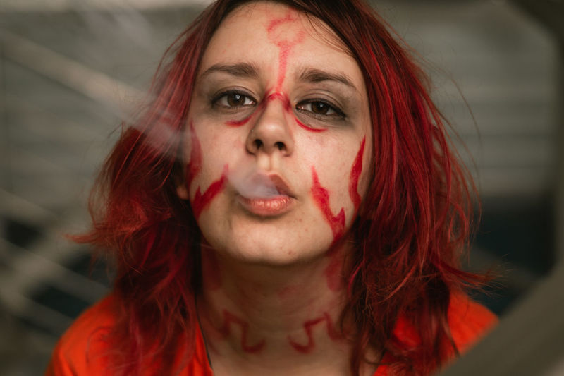 Close-up portrait of woman exhaling smoke