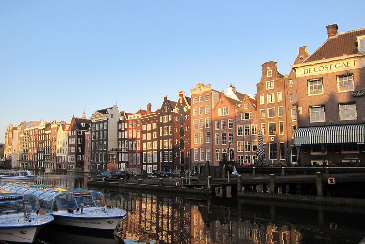 Sailboats moored on canal by buildings against sky in city