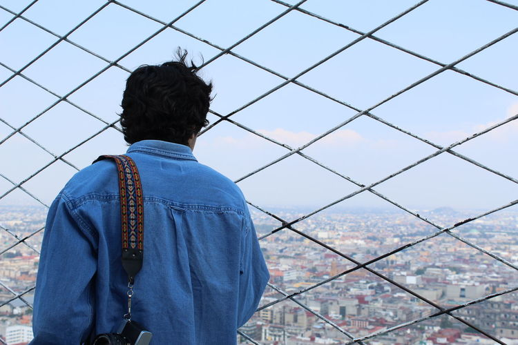 Rear View Of Man Looking At Cityscape While Standing At Observation Point