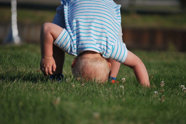 Playful baby boy with headstand on grassy field