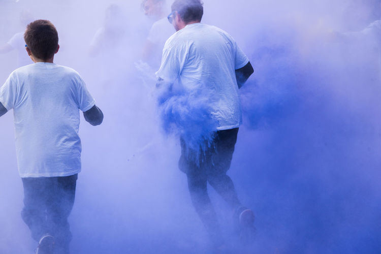 People running amidst powder paint in city