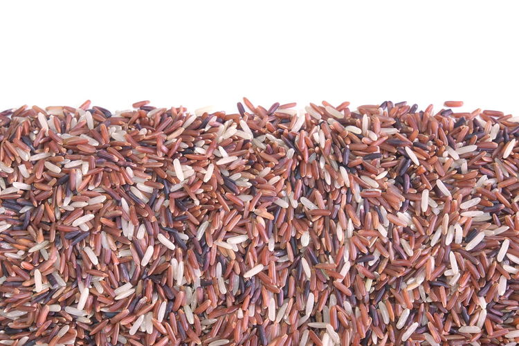 Close-up of brown rice on white background