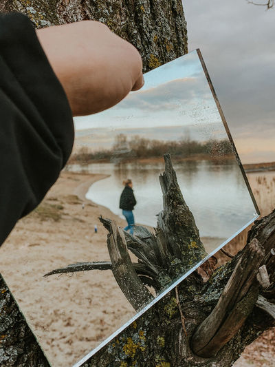 Man fishing on lake against sky