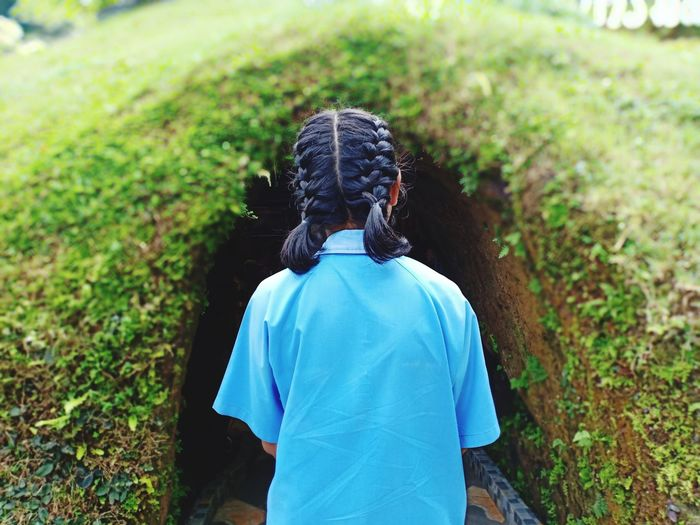 Rear View Of Girl Standing Against Grassy Tunnel