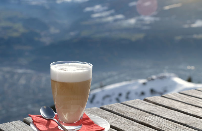 Glass of latte macchiato caffee latte on a wooden table and sunray. snow covered mountain background