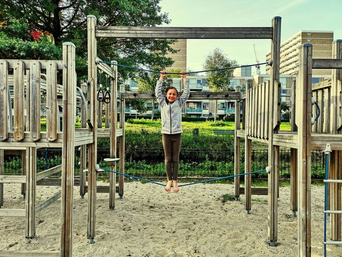 Portrait Of Smiling Girl Standing On Rope In Playground