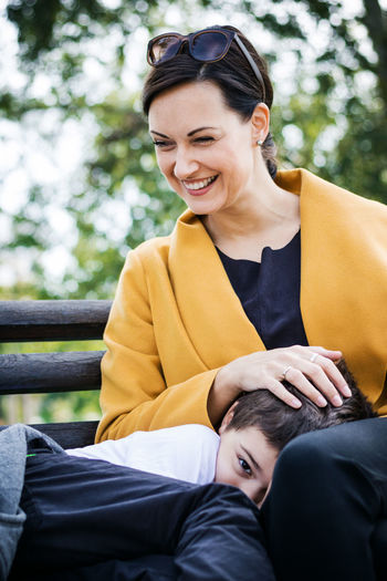 Smiling woman sitting with son at public park